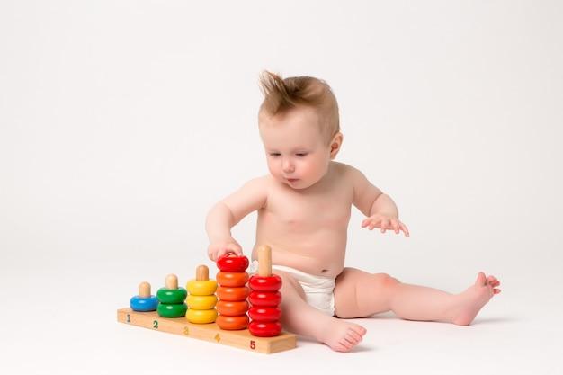 Bebê fofo com brinquedo de desenvolvimento em um fundo branco Foto Premium