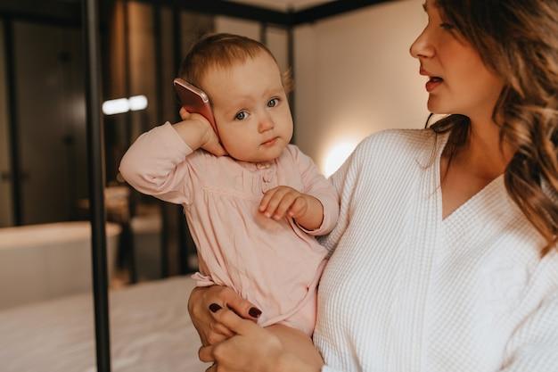 Bebê fofo com roupas de casa suavemente rosa está segurando o telefone enquanto sua mãe a abraça no fundo da cama. Foto gratuita