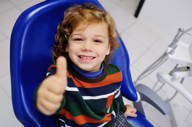 Bebê fofo em um suéter listrado na recepção no dentista com polegares para cima Foto Premium