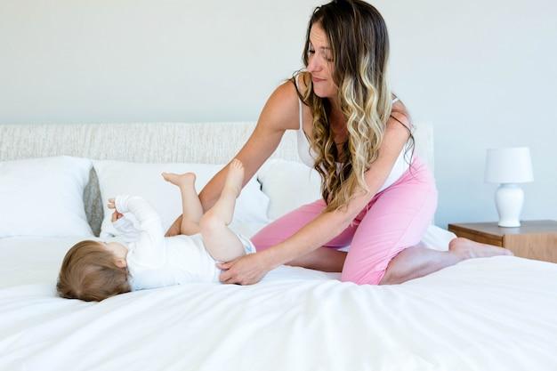 Bebê fofo está tentando rolar na cama enquanto uma mulher morena a segura Foto Premium
