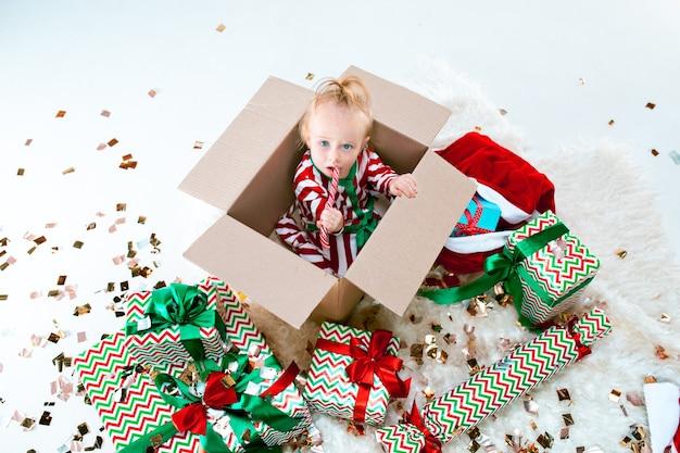 Bebê fofo menina de 1 ano de idade sentada em uma caixa sobre fundo de decoração de natal. feriado, celebração, conceito de criança Foto gratuita
