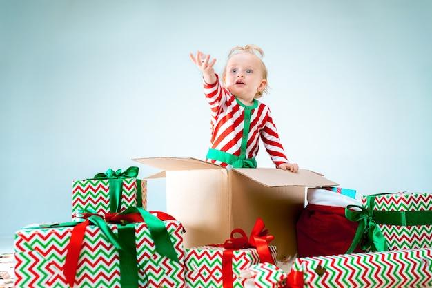 Bebê fofo menina de 1 ano de idade sentada na caixa sobre o fundo de natal. feriado, celebração, conceito de criança Foto gratuita