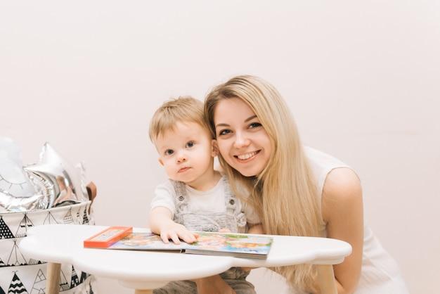 Bebê fofo sentado à mesa e lendo um livro com sua mãe nas cores brilhantes do berçário. Foto Premium