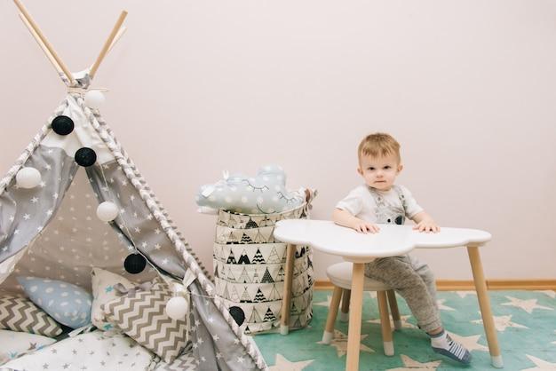 Bebê fofo sentado à mesa no quarto das crianças em tons de brancos, cinza e azuis. perto da tenda e um saco de brinquedos Foto Premium