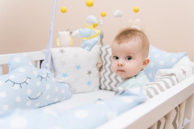 Bebê fofo sentado em uma cama redonda branca. creche leve para crianças pequenas. brinquedos para berço infantil. criança sorridente, brincando com móveis de feltro no quarto ensolarado. Foto Premium