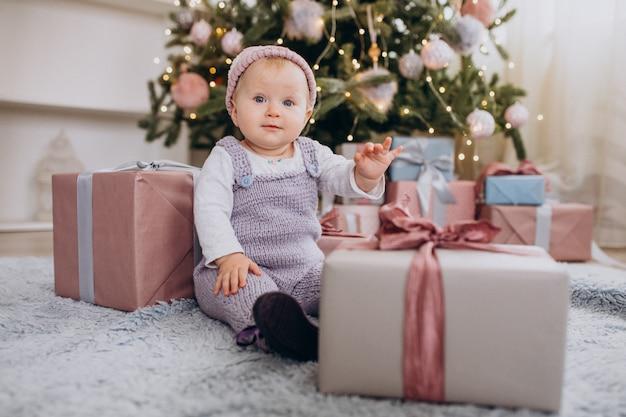Bebê menina bonitinha sentada perto de presentes de natal Foto gratuita