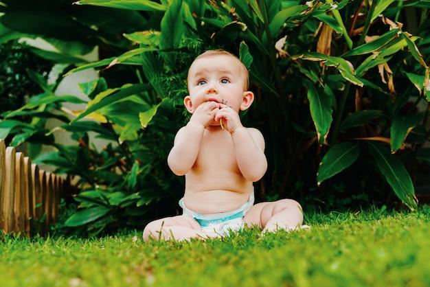 Bebê na fralda sem roupa que senta-se na grama que mordisca uma flor. Foto Premium