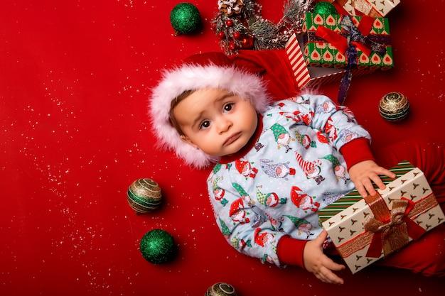 Bebê papai noel em fundo vermelho, espaço para texto Foto Premium