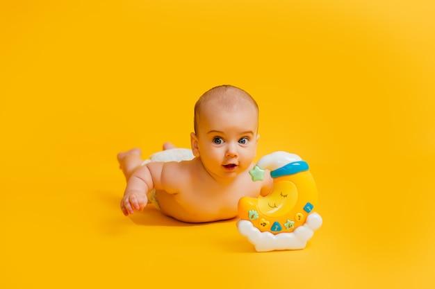 Bebê pequeno deitado de bruços com lua de brinquedo Foto Premium