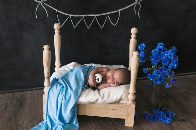 Bebê pequeno exigente dormindo na cama pequena Foto gratuita
