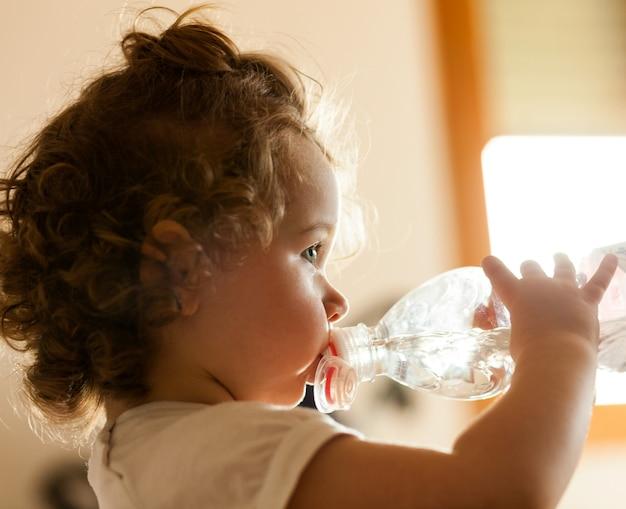 Bebé pequeno que bebe a água fresca. Foto Premium