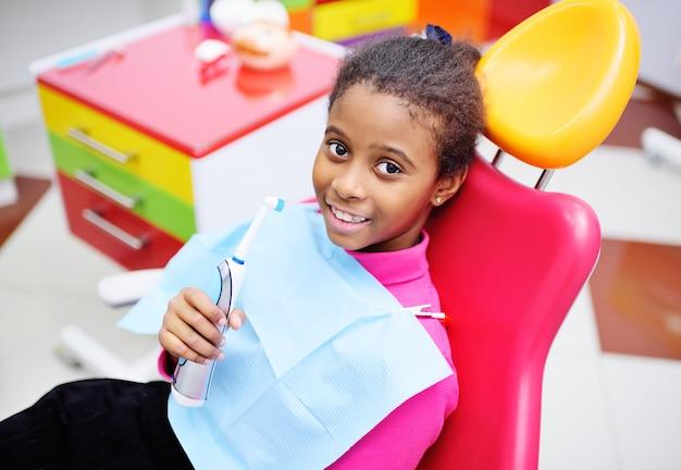 Bebé preto bonito que sorri sentando-se em uma cadeira dental vermelha no exame no dentista das crianças Foto Premium