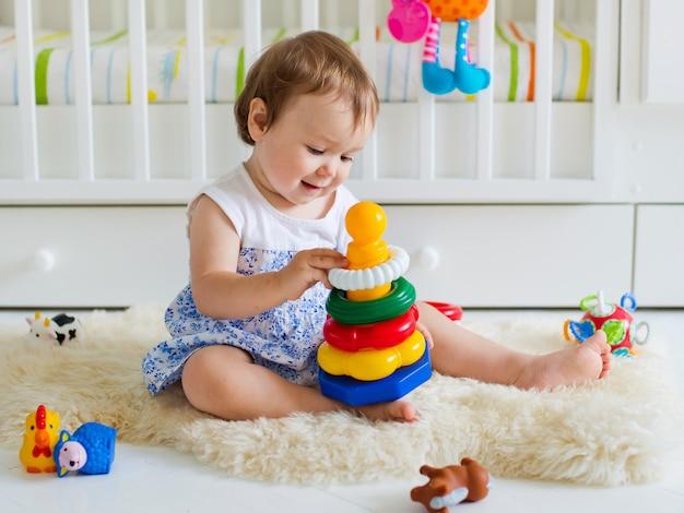 Bebé que joga com o brinquedo educacional no berçário Foto Premium