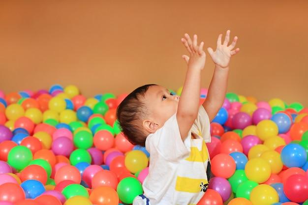 Bebé que joga com o campo de jogos plástico colorido das esferas. Foto Premium