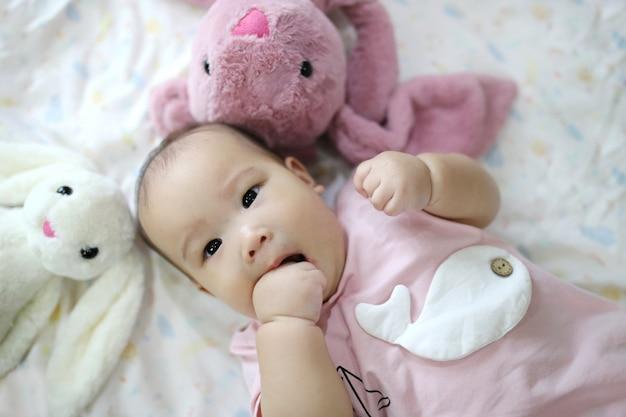 Bebê recém-nascido asiático esperto bonito que dorme com o brinquedo do coelho da peluche na cama macia cor-de-rosa em casa. Foto Premium