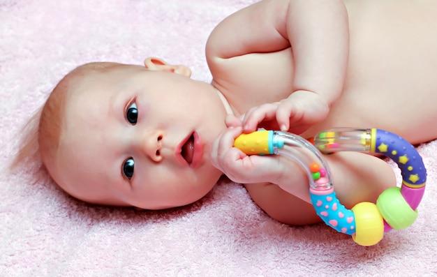 Bebê recém-nascido brincando com chocalho colorido Foto Premium