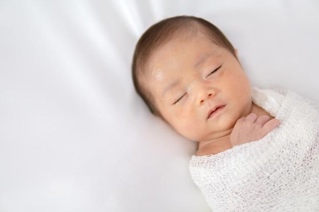 Bebê recém-nascido de sono no envoltório branco quando no fundo geral branco. Foto Premium