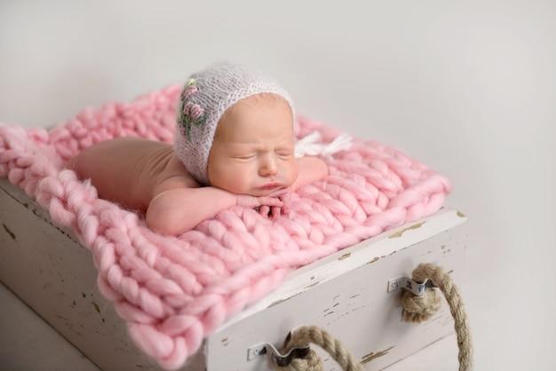 Bebê recém-nascido dormindo com bochechas gordinhas deitado na caixa no tapete Foto Premium