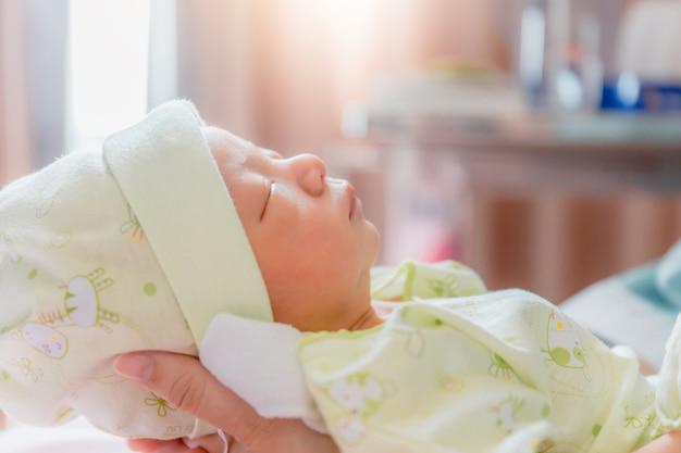Bebé recém-nascido dormindo na mão da mãe asiática no hospital Foto Premium