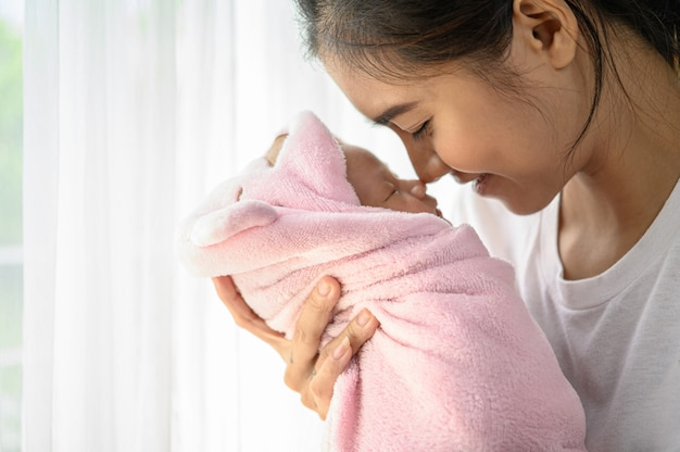 Bebê recém-nascido dormindo nas mãos da mãe e o nariz colidiu Foto gratuita