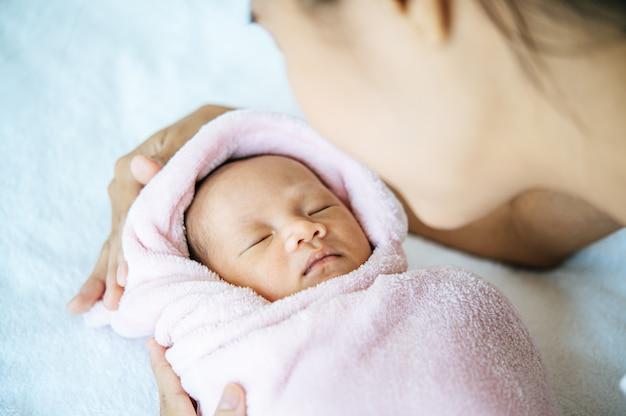Bebê recém-nascido dormindo nos braços da mãe Foto gratuita