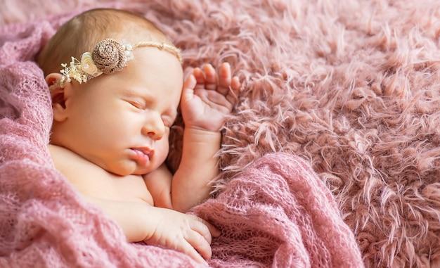 Bebê recém-nascido dormindo sobre um fundo rosa. foco seletivo. pessoas. Foto Premium