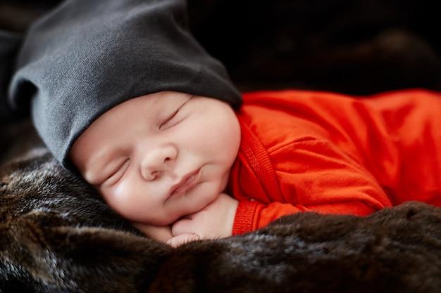Bebê recém-nascido está deitado no sofá. bebê Foto Premium