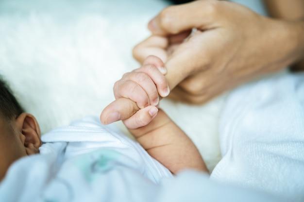Bebê recém-nascido, mãe de mãos dadas Foto gratuita