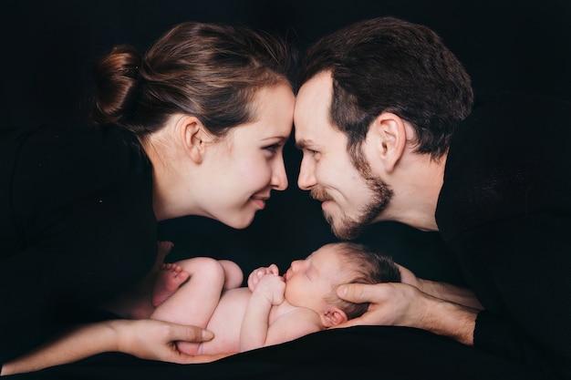 Bebê recém-nascido que encontra-se nas mãos dos pais em um fundo preto. imitação de um bebê no útero. Foto Premium
