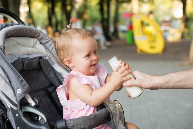 Bebê segurando uma mamadeira em um carrinho de bebê Foto Premium