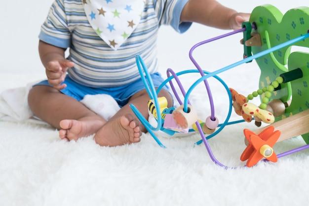 Bebê sentado e brincar de brinquedos de madeira, brinquedo de foco Foto Premium