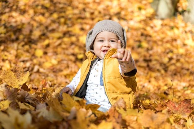 Bebê sorridente apontando para alguém Foto gratuita