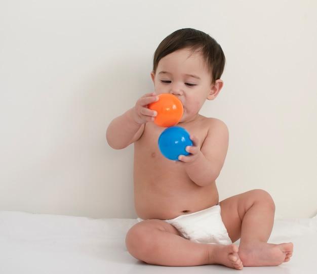 Bebê usa fralda branca de eliminação está jogando com bolas de plástico coloridas Foto Premium