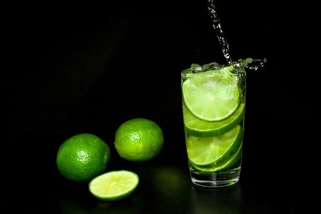 Beber com gelo e limão verde maduro fresco em preto Foto Premium