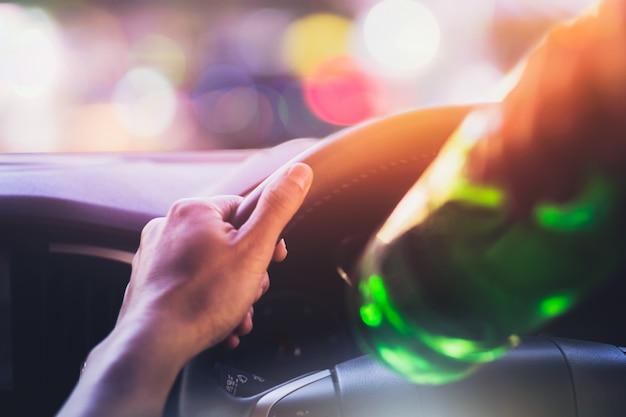 Beber e dirigir, homem bebendo álcool enquanto dirigia o carro depois da festa durante a noite Foto Premium