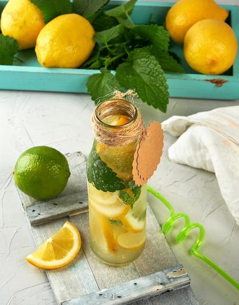 Beber limonada em uma garrafa de vidro e limões frescos maduros Foto Premium