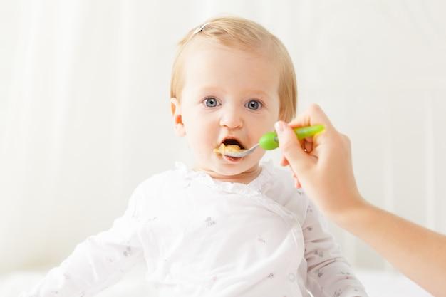 Bebezinho, alimentando-se com uma colher Foto Premium