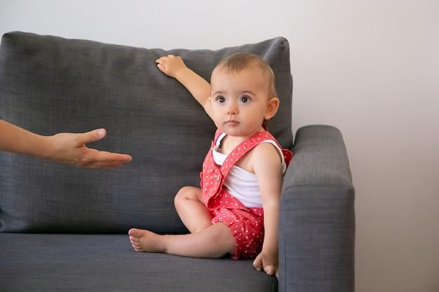 Bebezinho engraçado sentado no sofá cinza e olhando para uma pessoa irreconhecível. alguém dando a mão à adorável garotinha em shorts de macacão vermelho. família, infância e conceito de estar em casa Foto gratuita