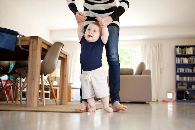 Bebezinho feliz aprendendo a andar com a mãe ajuda em casa Foto Premium