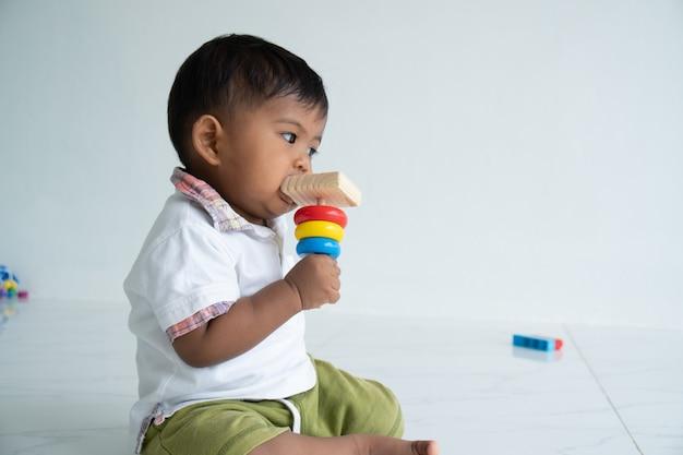 Bebezinho jogar brinquedo de madeira no quarto Foto Premium