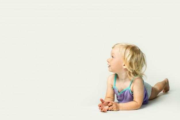 Bebezinho lindo sorrindo, olhando para o lado enquanto estava deitado de bruços Foto Premium