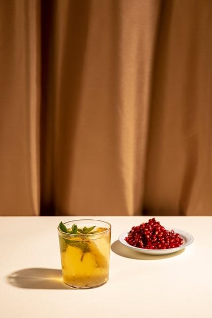 Bebida cocktail com sementes de romã na mesa branca Foto gratuita