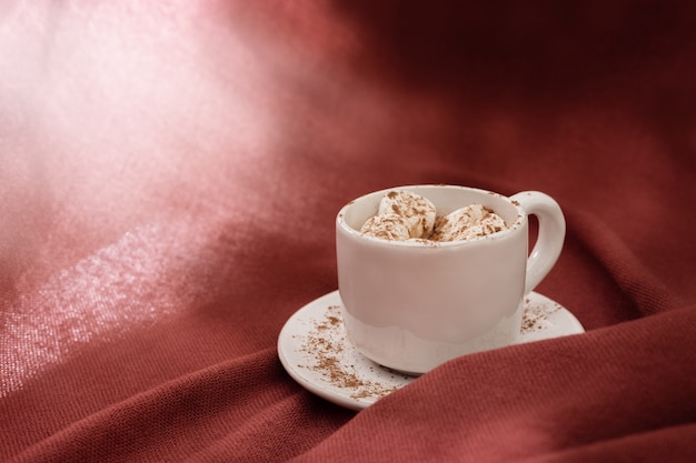 Bebida de cacau doce quente com marshmallow, luz do sol brilhante, texturizado fundo de têxteis Foto Premium