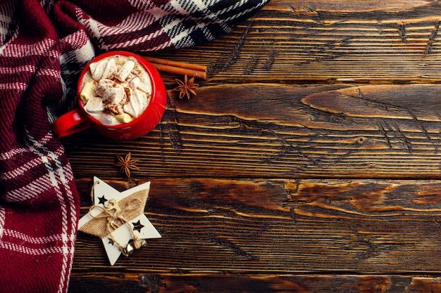 Bebida de café de inverno, cacau com chantilly e marshmallows em uma xícara de cerâmica vermelha Foto Premium