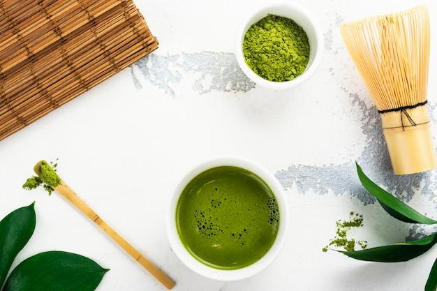 Bebida de chá matcha verde e acessórios de chá no fundo branco Foto Premium