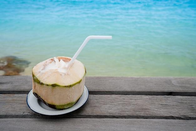 Bebida de coco na ilha de praia de areia do oceano Foto Premium