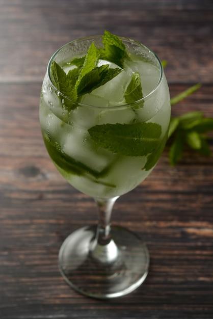 Bebida de coquetel de verão em copo de vinho. bebida refrescante com folhas de hortelã, gin tônica, xarope. . Foto Premium
