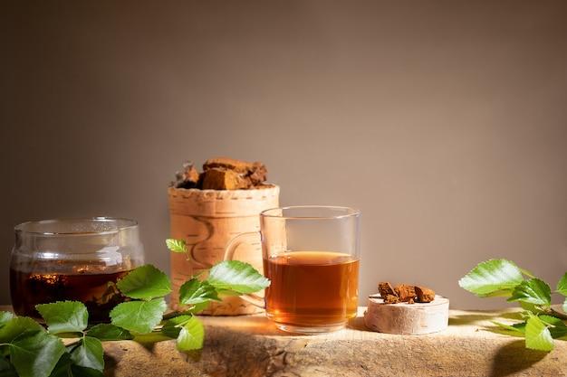Bebida de cura de bétula chaga cogumelo, pedaços de cogumelo chaga, galhos na prancha de madeira em pano de fundo bege. copie o espaço. Foto Premium