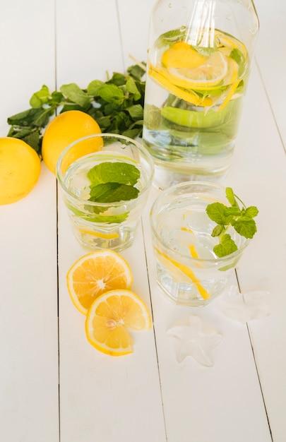 Bebida de limão em garrafa e copos Foto gratuita