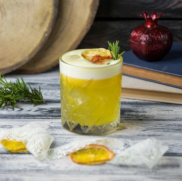 Bebida de limão, guarnecida com fatia de limão seca, rosemarine em copo de cristal Foto gratuita